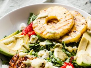 Grilled chicken with cilantro sauce, pineapple rings in the background.