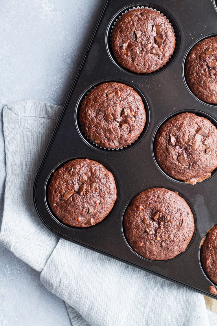 Chocolate muffins in a muffin tin, blue background.