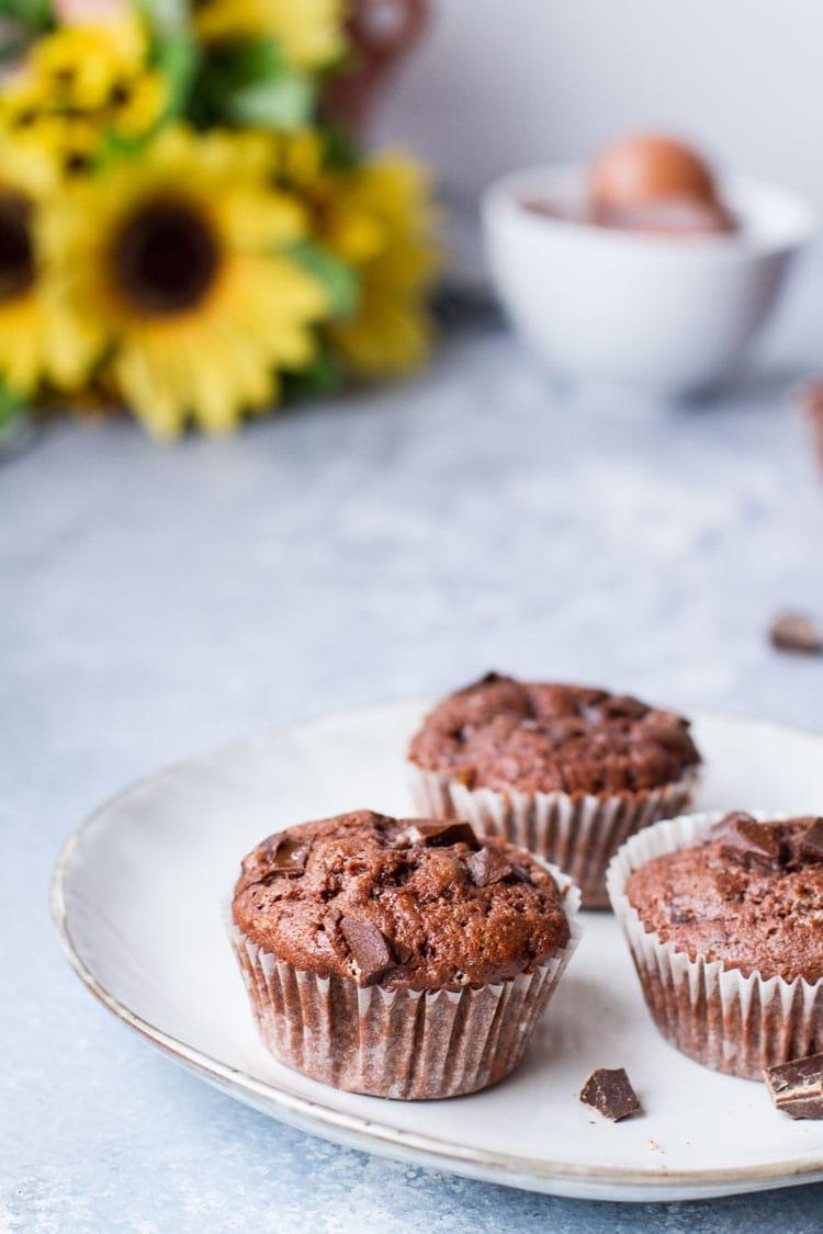 Three chocolate banana muffins on a plate.