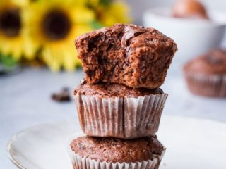 Three chocolate muffins stacked on top of each other, the top one is taken a bite out of.
