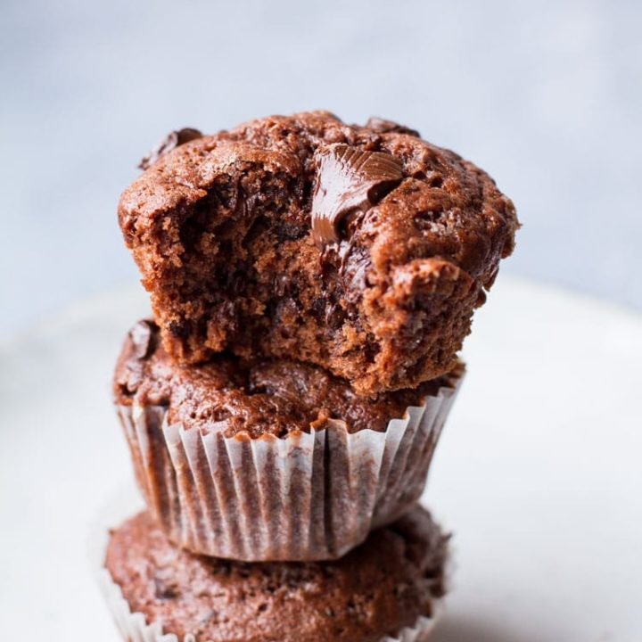 Three banana muffins stacked on each other, one taken a bite out of and chocolate is melting on top.