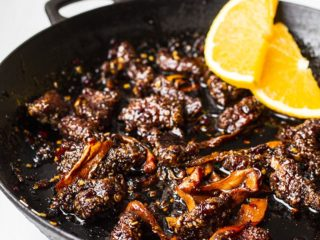 Close-up of beef and carrots in a skillet.
