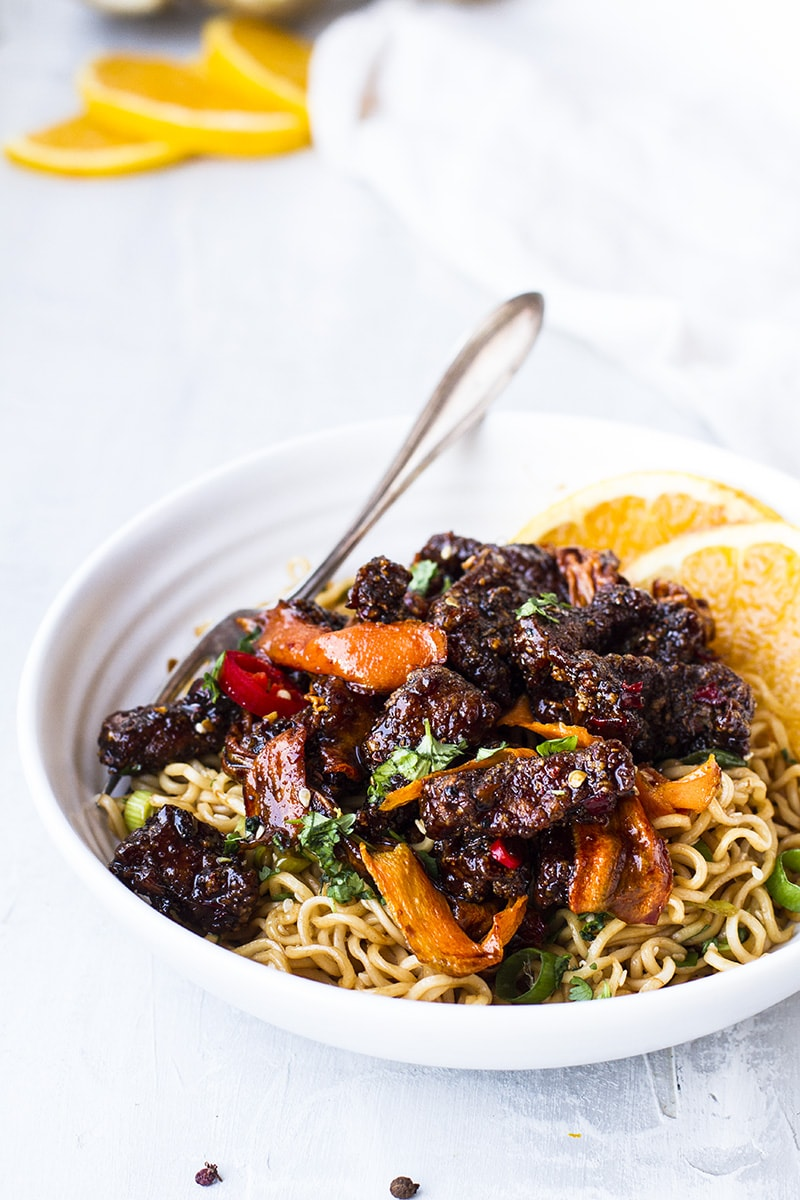 White bowl with noodles, beef and carrots.