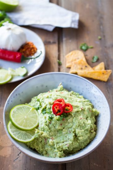 Chunky guacamole in a rustic bowl, with lime slices.