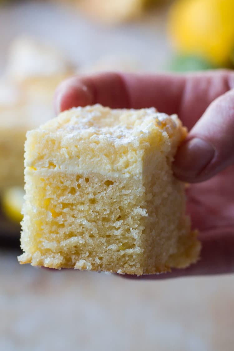 Hand holding one piece of lemon cake.