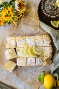 Lemon Cake with lemon slices and powdered sugar on top. Background is parchment paper and a green towel. Some yellow flowers and lemons in the corner.