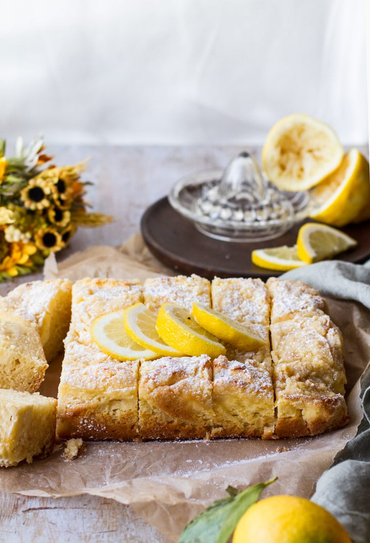 Lemon Cake with lemon slices and powdered sugar on top. Background is parchment paper and a green towel,