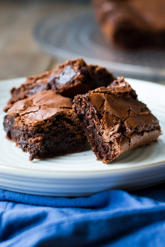 Three slices of brownies on a white plate. Blue fabric underneath.