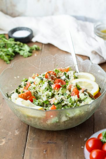 Tabbouleh and lemon wedges in a large glass bowl. Ingredients and towel blurred in the background.