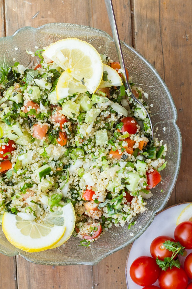 Tabbouleh with quinoa and lemon slices in a large glass bowl. Flatlay.