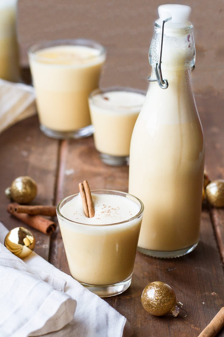 A glass and a small bottle of eggnog. Glass garnished with cinnamon stick.