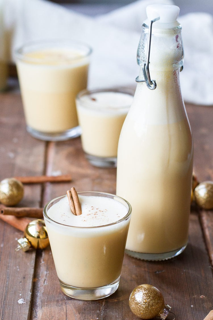 Glass and bottle with eggnog. Gold ornaments around on a wooden table.