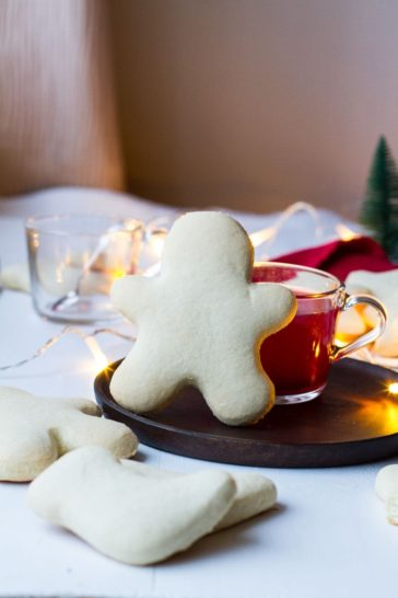 A standing cookie man on a wooden plate. Leaning on a glass mug with red mulled wine.