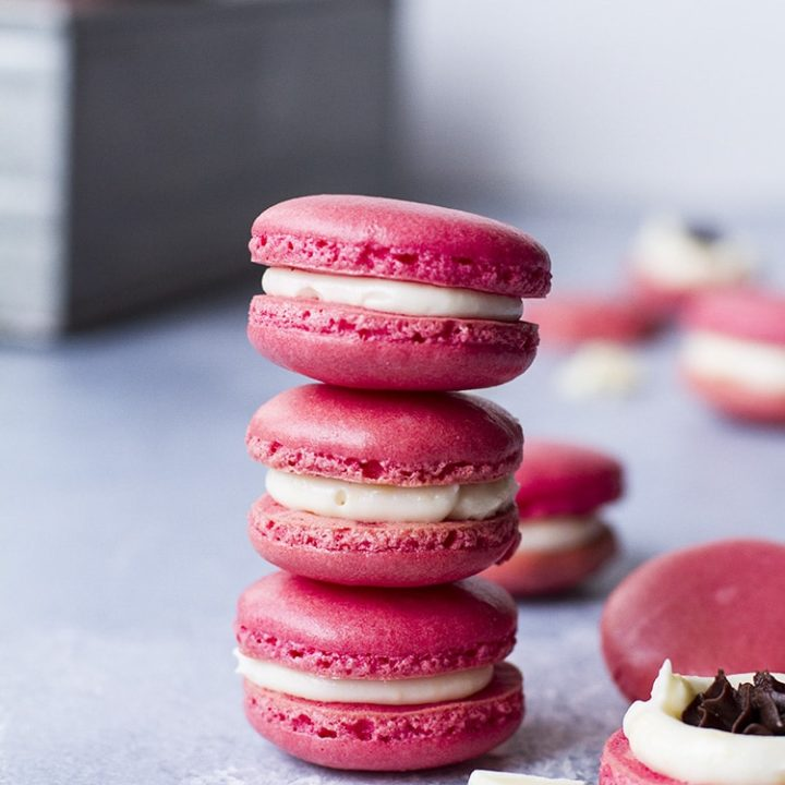 Three pink macarons stacked on top of each other.