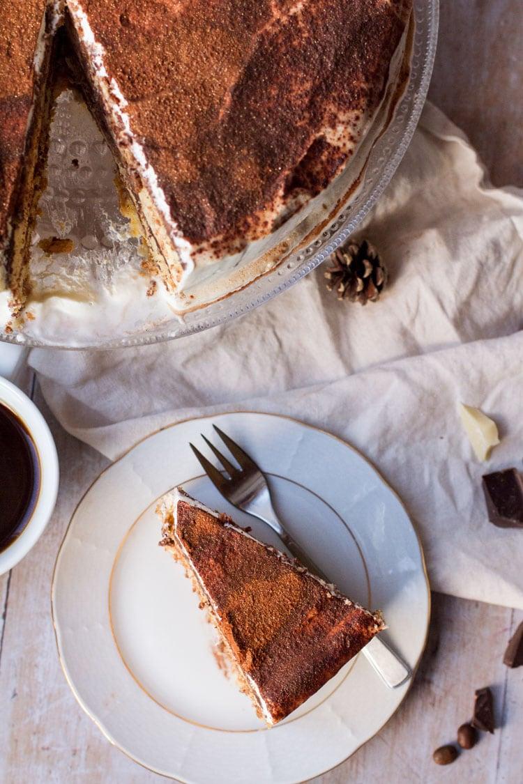 Slice of tiramisu cake and the whole cake in the corner, flatlay.