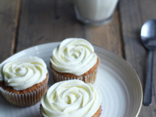 Three cupcakes with white frosting shaped as roses. Milk in the background.