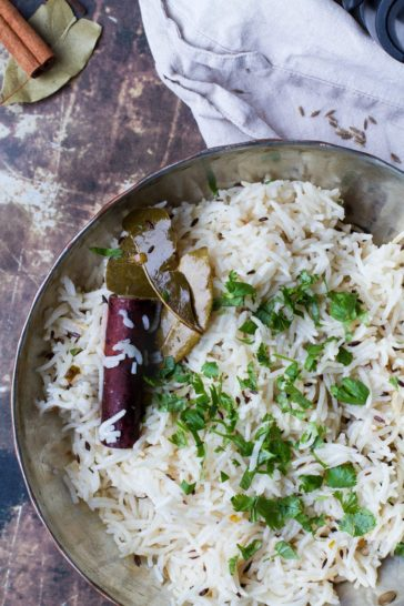 Bird's eye view of a metal pan with Indian rice with cilantro, cinnamon stick and bay leaf. Rusty background and nude colored cloth.