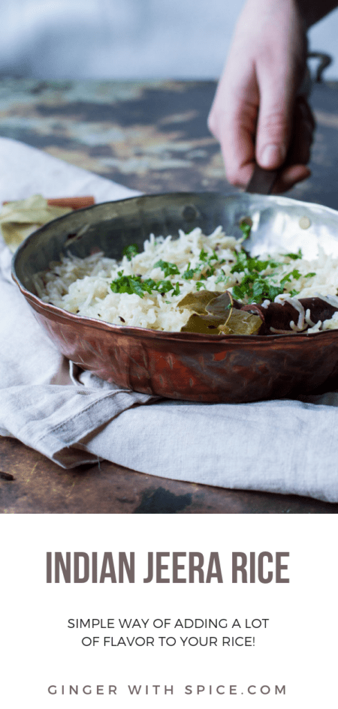 Straight angle of a copper pan with Indian rice with cilantro, cinnamon stick and bay leaf. Hand holding the pan's handle. Rusty background and nude colored cloth. Pinterest pin