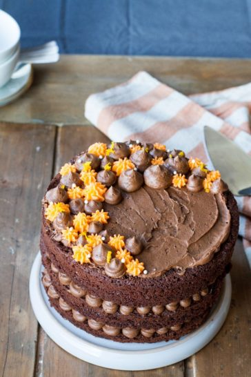 Orange chocolate cake with chocoate and orange colored buttercream on top.
