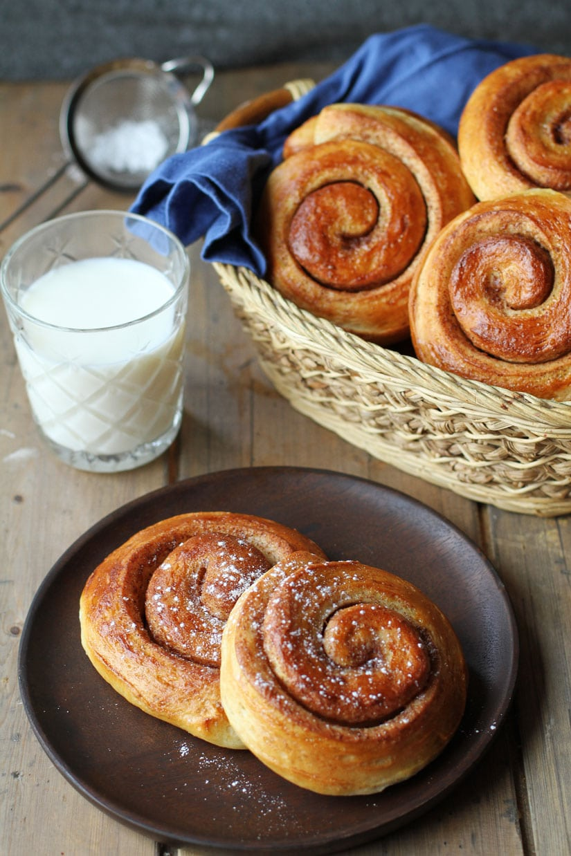 Cinnamon rolls on a wooden plate. More in the background.
