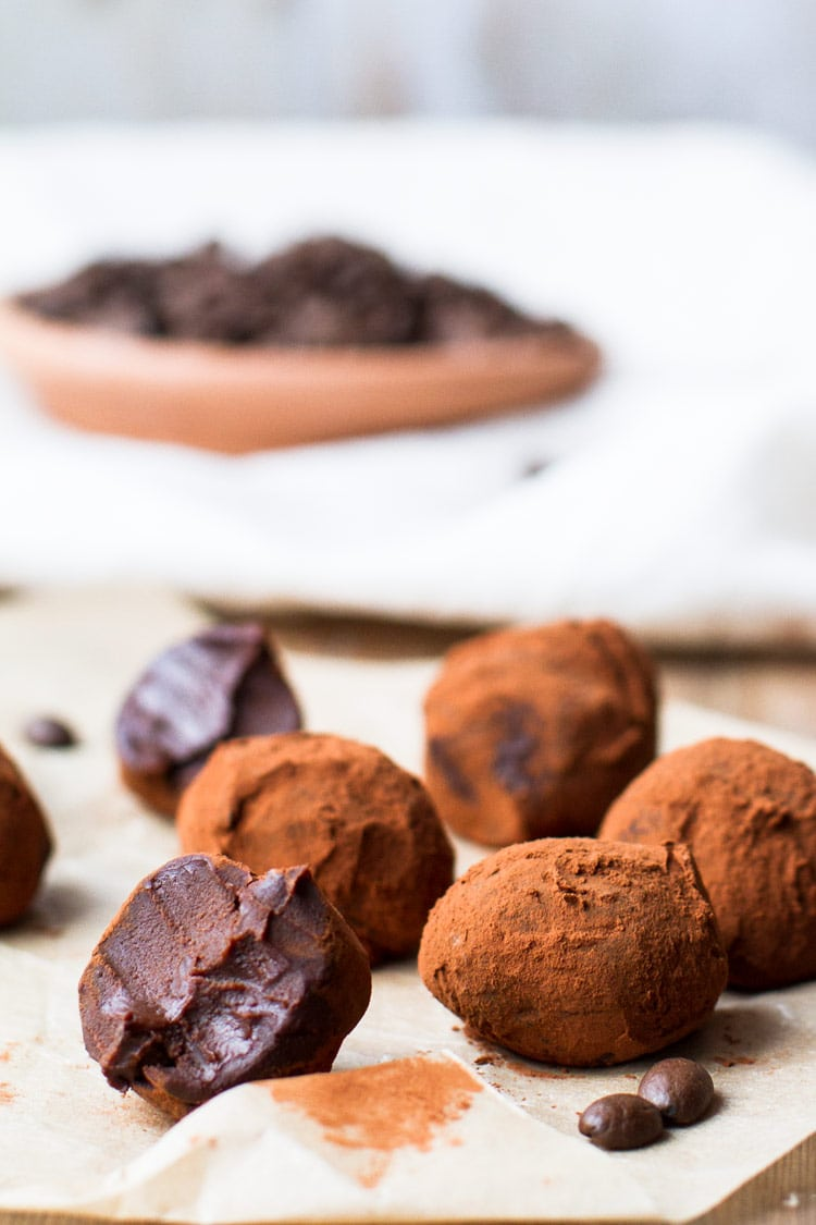 Chocolate Coffee Truffles on brown parchment paper. One is taken a bite of. Covered in cocoa powdered. A plate of coffee beans in the background.