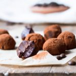 Chocolate Coffee Truffles on brown parchment paper. One is taken a bite of. Covered in cocoa powdered.