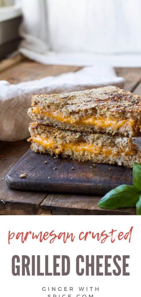 Parmesan crusted grilled cheese sandwich on a wooden cutting board.