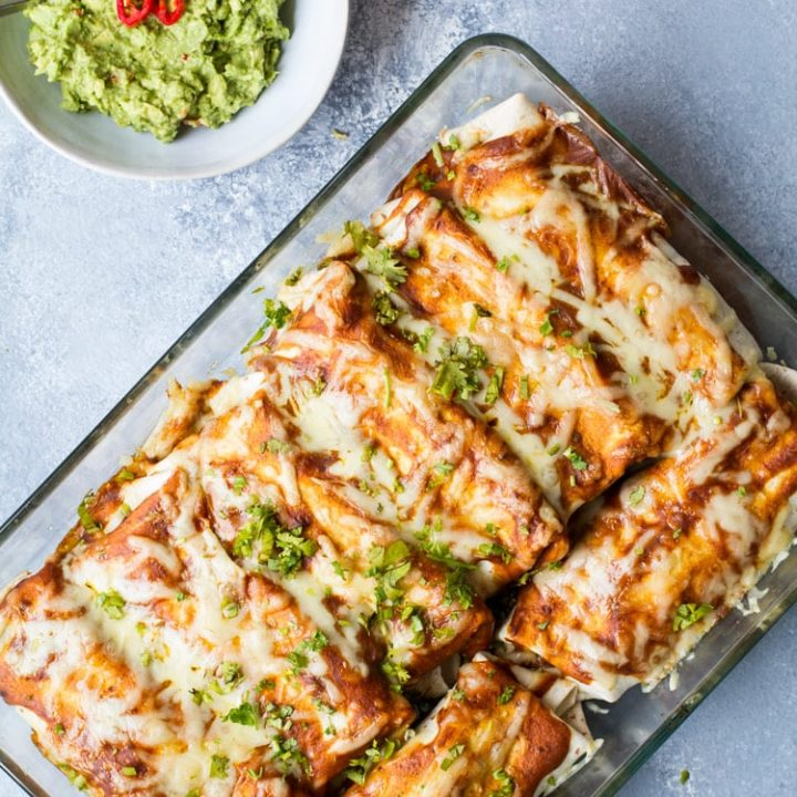 Beef and beans enchiladas in a clear casserole.