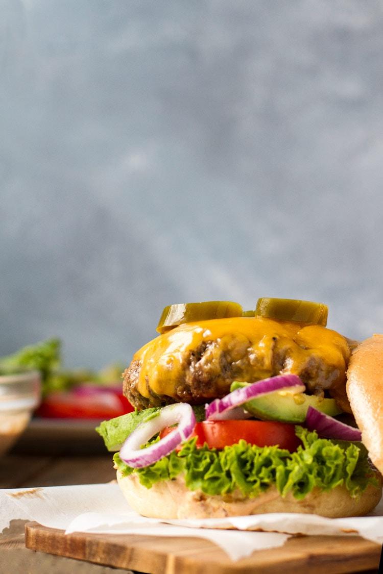Chipotle cheddar burger on a burger bun bottom and greens but no bun topping.