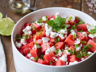 Watermelon salad in a white bowl on a wooden table.