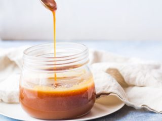 Glass jar with salted caramel sauce, hand with spoon drizzling into the jar.