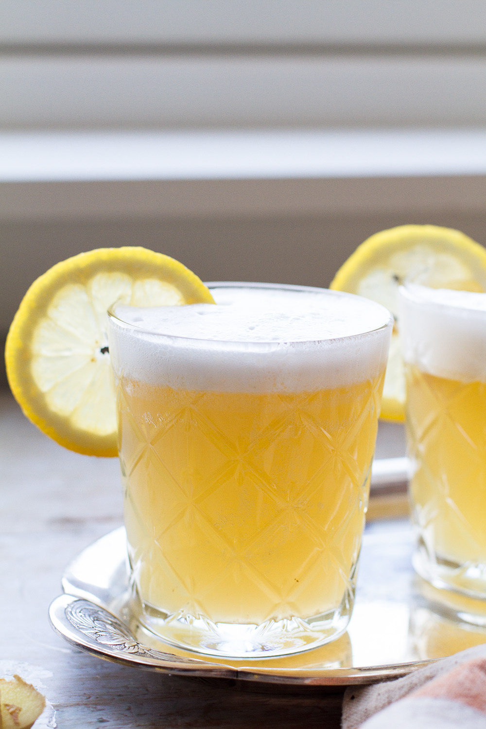 A glass with whiskey sour with backlight to show the yellow color of the drink.