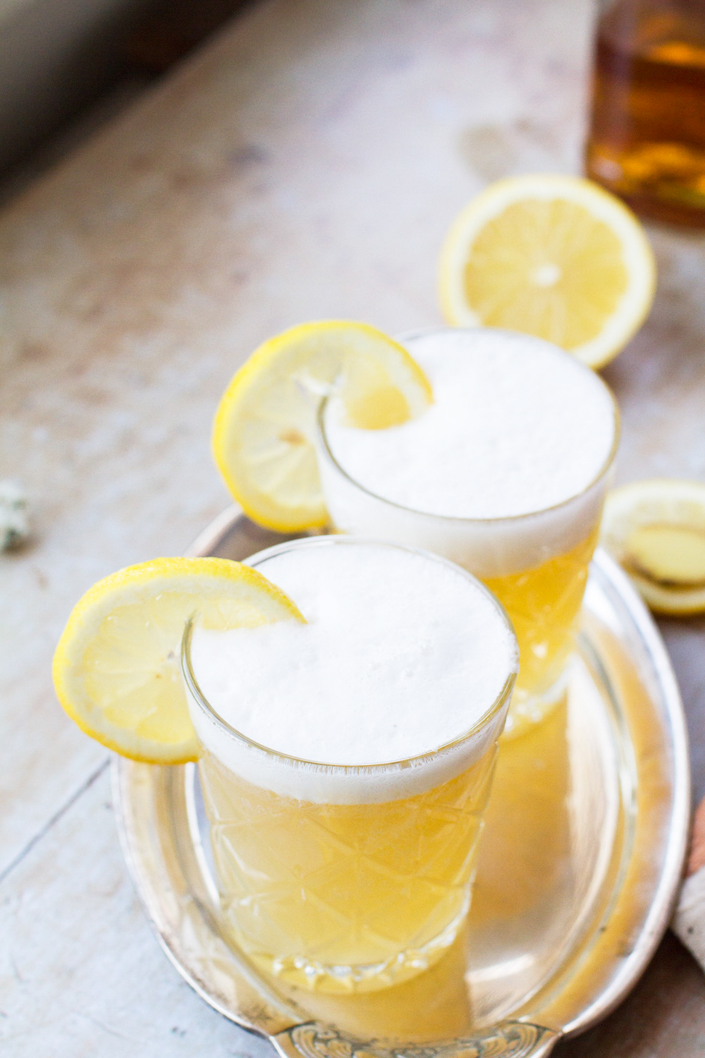 Two glasses with whiskey sour and a frothy top, garnished with lemon slices.