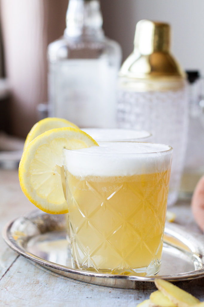A tumbler glass with whiskey sour and a frothy top.