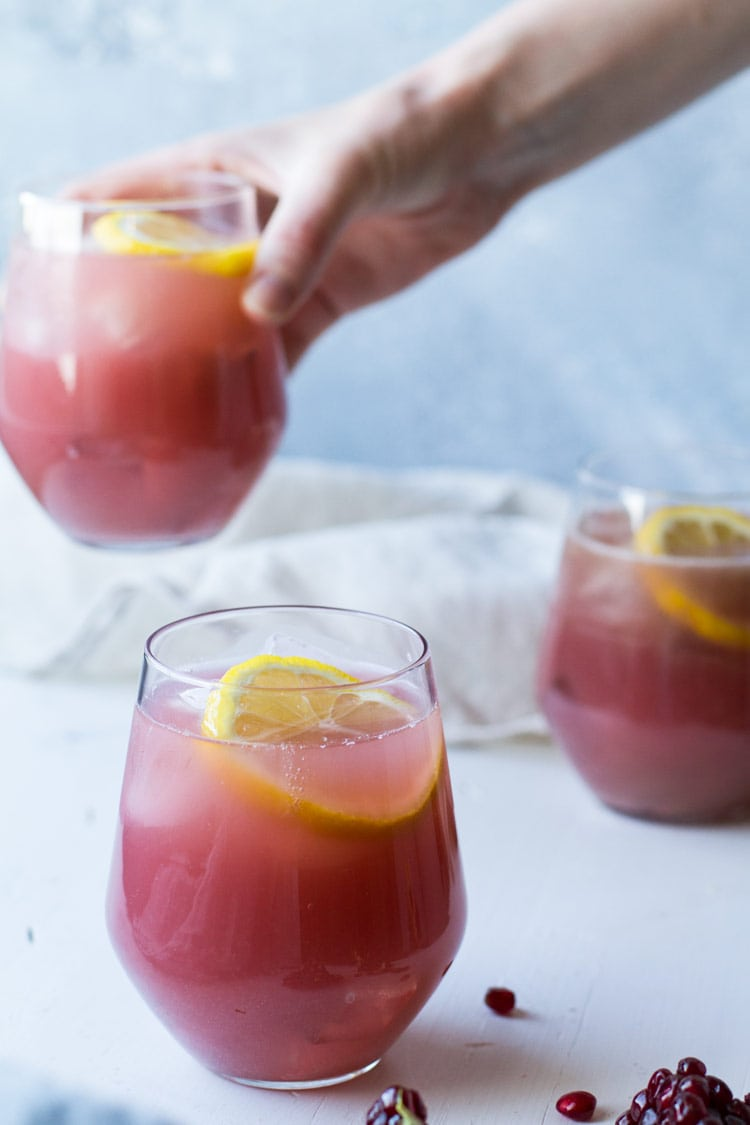 Three glasses with pink pomegranate lemonade, hand taking one of them.