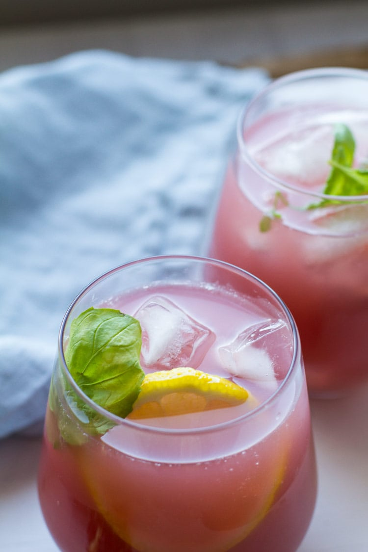 Two glasses with pink lemonade, garnished with ice cubes and mint sprig.