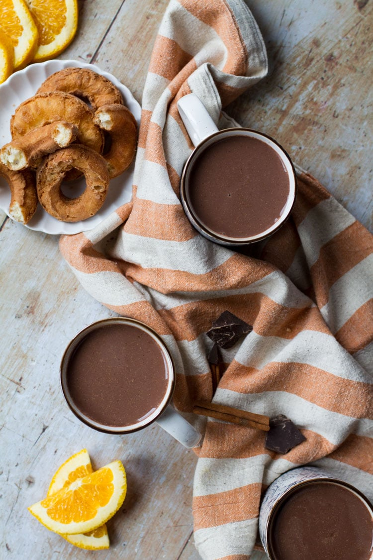 Two cups with hot chocolate, one orange striped towel between them and donuts on the side. Flatlay.