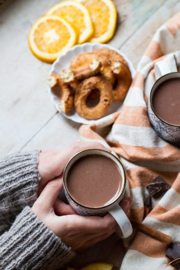 Hands holding a cup of orange hot chocolate. Donuts in the background.