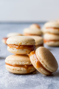 Salted Caramel Macarons with Homemade Caramel stacked with blurred macarons in the background.