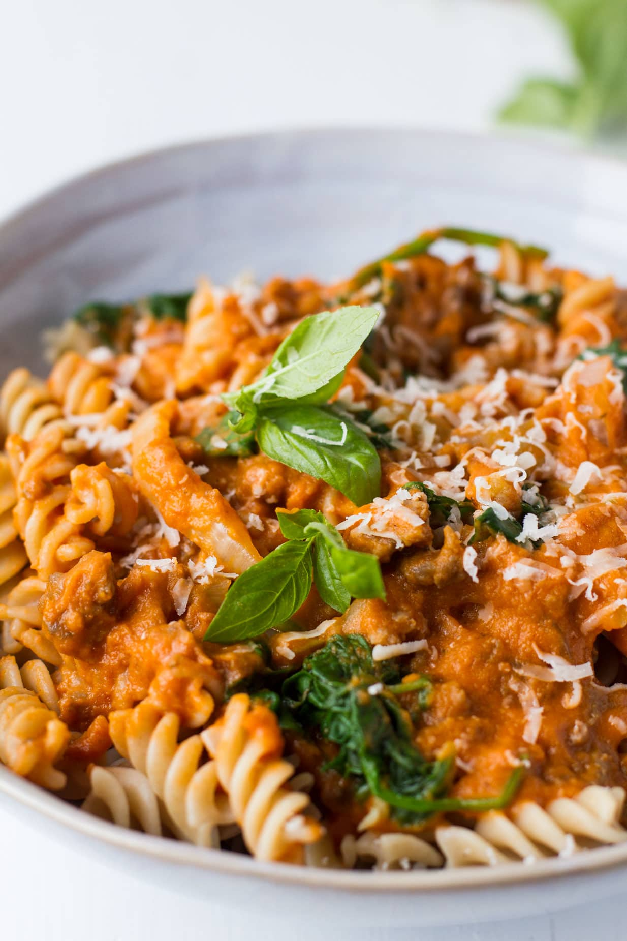 Creamy Parmesan Pumpkin Pasta, closeup with a basil garnish.