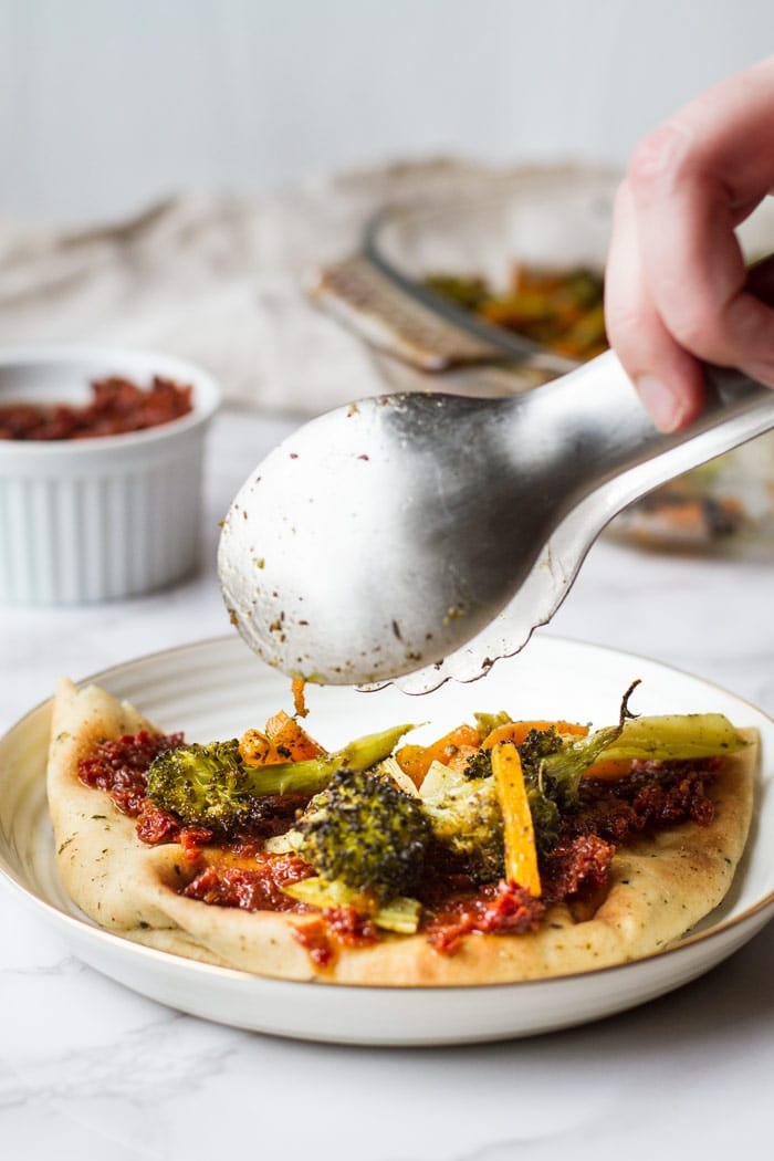 Naan with sun-dried tomatoes and adding roasted broccoli and carrots with a metal tong.
