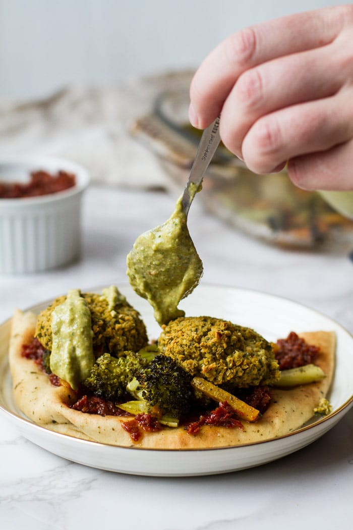 A naan with sun dreid tomatoes, roasted vegetables, baked falafel and drizzling avocado sauce with a spoon.