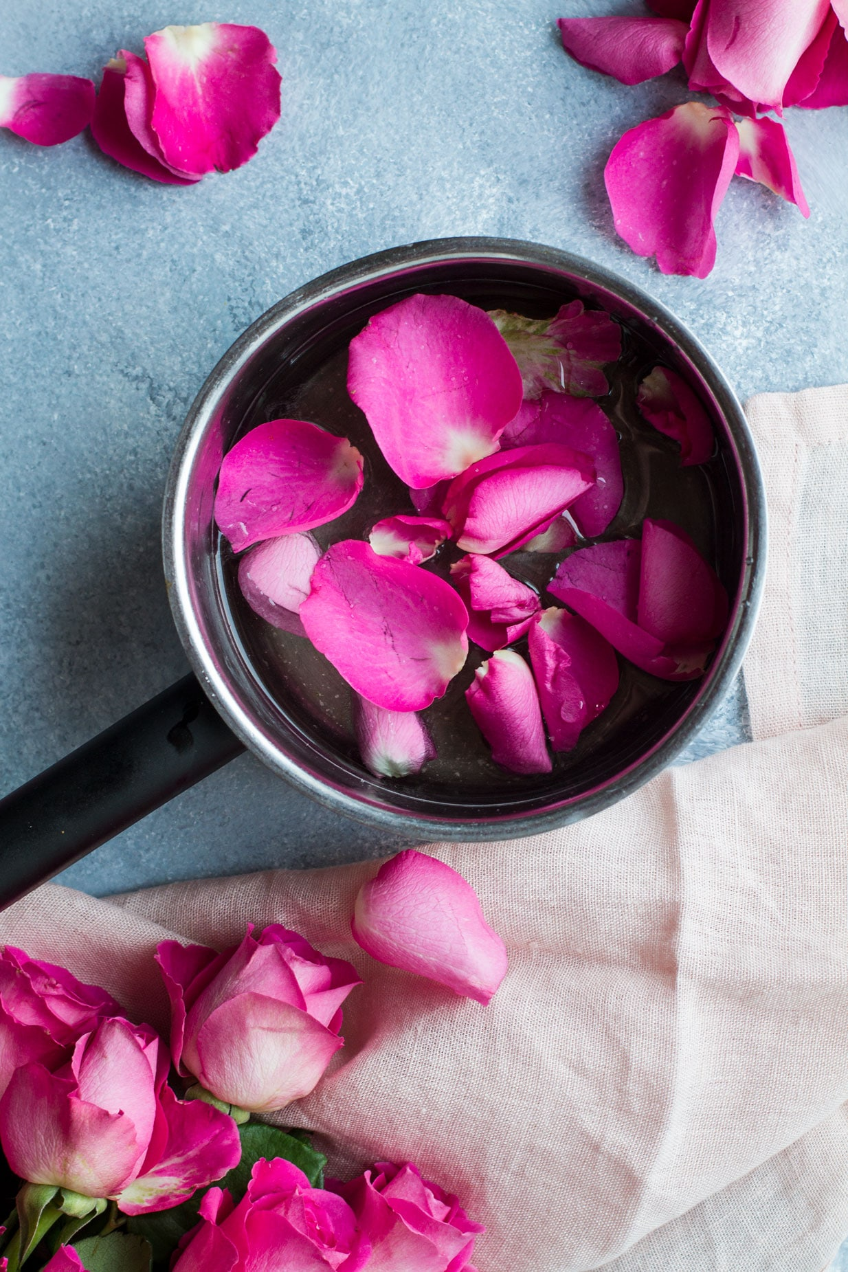 Bird's eye view of a saucepan with pink rose petals. Roses in the bottom left corner, blue background and pink cloth.
