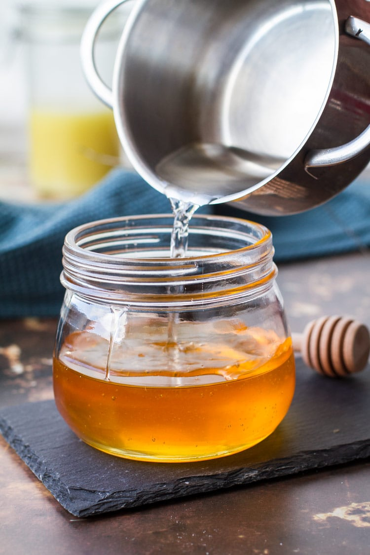 Pouring warm water in a jar of honey. On a stone plate.