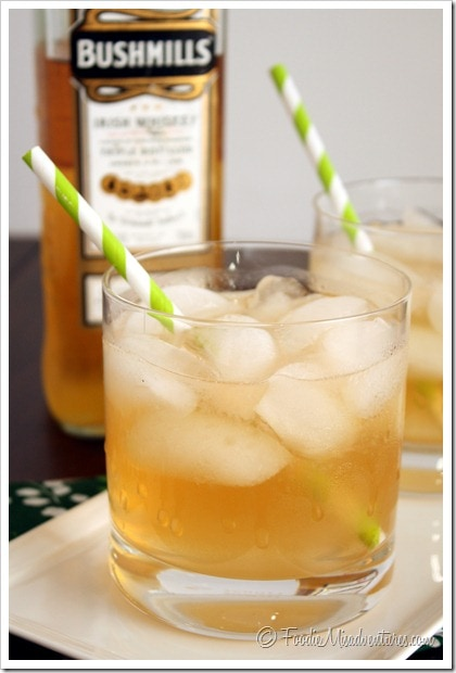 Irish Maiden Whiskey cocktail in a rock glass with ice cubes and green straw.