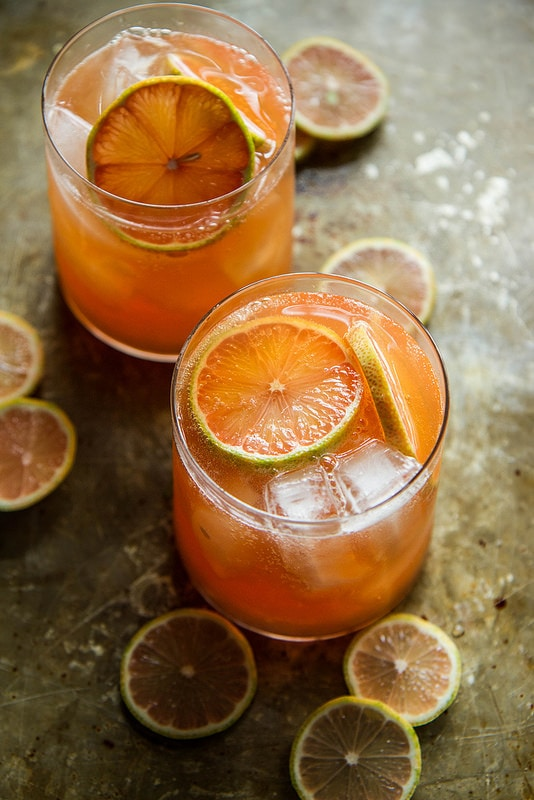 Grapefruit whiskey sour in rocks glasses with citrus garnish.