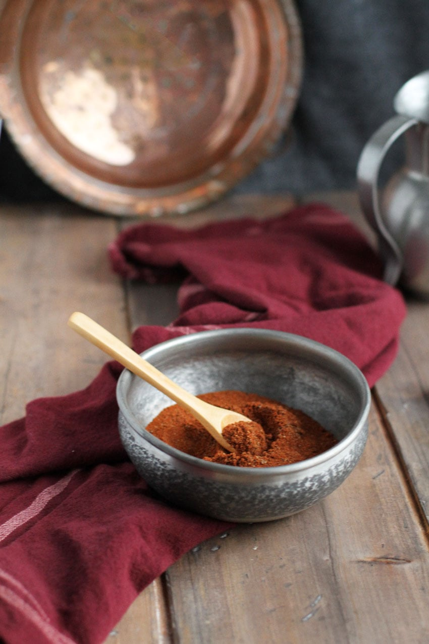 Baharat spices in a metal bowl and wooden spoon. Copper and wooden background.