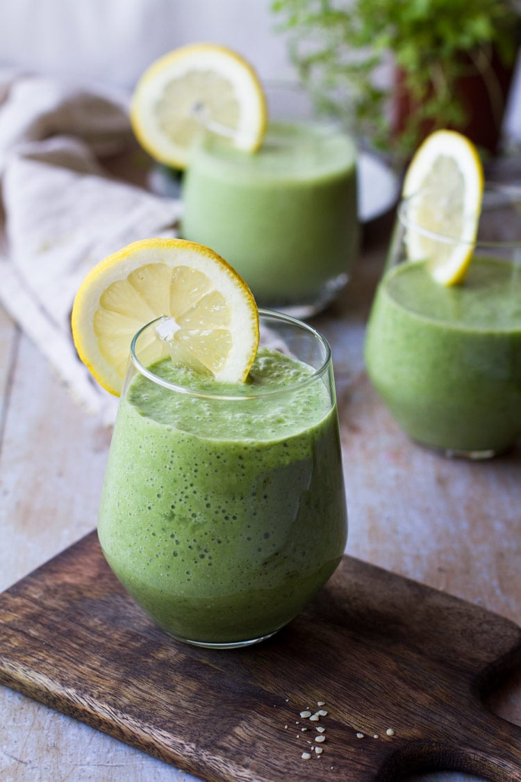 Green smoothie recipe with lemon wedge on glass rim.