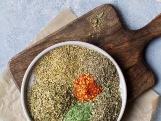 Small plate on a wooden cutting board with unmixed spices of Italian seasoning.