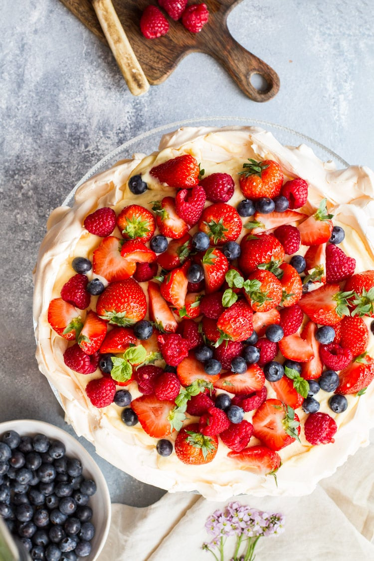 Flatlay of this pavlova recipe with fresh berries. A bowl of blueberries on the side.